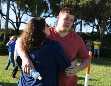 Deux étudiants se consolent après une fusillade dans leur lycée qui a coûté la vie à 17 personnes ( Michele Eve Sandberg (AFP) )