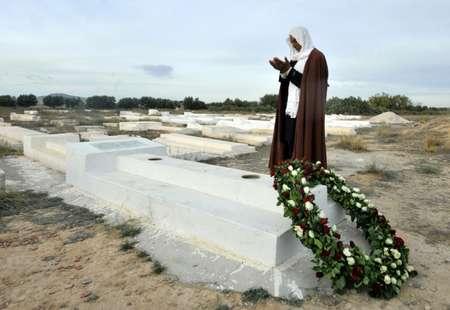 تونسي يصلي في 23 تشرين الثاني/نوفمبر 2015 امام قبر محمد البوعزيزي بائع الخضار الذي احرق نفسه في مدينة سيدي بوزيد في 2010  مطلقا شرارة