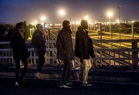 Des migrants traversent un pont au desssus des voies le 28 juillet 2015 au terminal d'Eurotunnel à Calais-Frethyn ( PHILIPPE HUGUEN (AFP) )