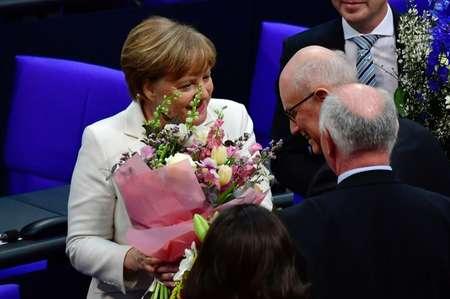 المستشارة الالمانية انغيلا ميركل (يسار) تتلقى تهنئة من رئيس كتلة المحافظين والاشتراكيين الديموقراطيين البرلمانية بعد اعادة انتخابها في 14 اذار/مارس. ( جون ماكدوغال (AFP) )