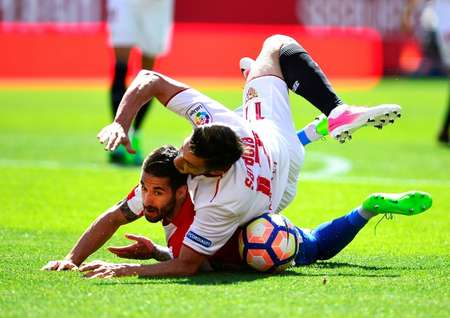 Sporting Gijon's Lillo Castellano (L) clashes with Sevilla's Pablo Sarabia during their Spanish league match at the Ramon Sanchez Pizjuan stadium in Sevilla, on April 2, 2017 ( CRISTINA QUICLER                     (AFP) )