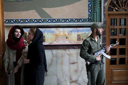Iranians queue to vote in presidential elections as a soldier stands guard at a polling station in Tehran on May 19, 2017 ( Behrouz MEHRI (AFP) )