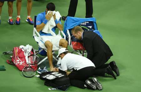 Medical staff check Novak Djokovic's foot during his 2016 US Open final match against Stan Wawrinka, at the USTA Billie Jean King National Tennis Center in New York, on September 11, 2016 ( Timothy A. Clary (AFP) )