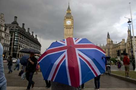 A pedestrian shelters from the rain beneath a Union flag themed umbrella as they walk near the Big Ben clock face and the Elizabeth Tower at the Houses of Parliament in central London on June 25, 2016 ( Justin Tallis (AFP) )