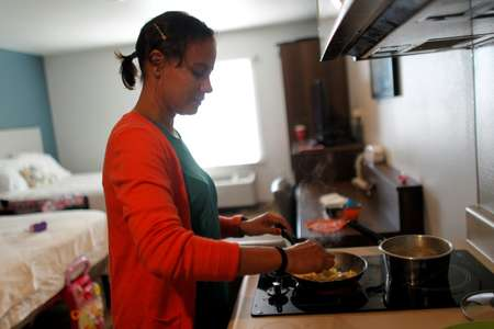 Debora Oquendo, 43, prepares breakfast for her and her 10-month-old daughter at the Orlando hotel they have been staying at since arriving from Puerto Rico ( Ricardo ARDUENGO (AFP) )