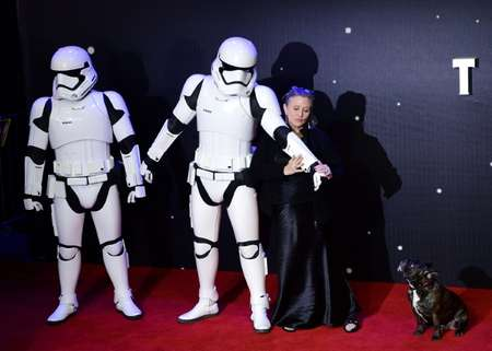 US actress Carrie Fisher (R) poses with a Storm Trooper as she attends the European Premiere of