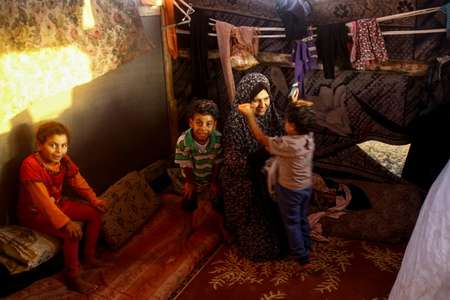 Noor and her children inside the family's shack near the beach in Gaza City ( MOHAMMED ABED (AFP) )