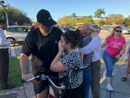 Des élèves sous le choc durant la fusillade au lycée Marjory Stoneman Douglas en Floride, le 14 février 2018 ( Michele Eve SANDBERG (AFP) )