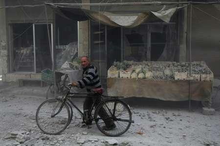 Un Syrien devant un commerce recouvert de poussière après une frappe aérienne dans la ville rebelle de Hamouria, dans la Ghouta orientale assiégée près de Damas, le 3 décembre 2017  ( Amer ALMOHIBANY (AFP) )