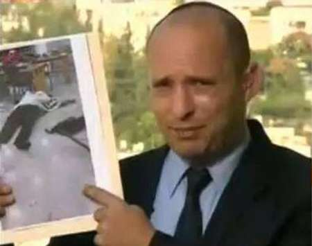 Israeli minister Naftali Bennet holding a picture of one of the victims in the Jerusalem synagogue attack, November 18, 2014