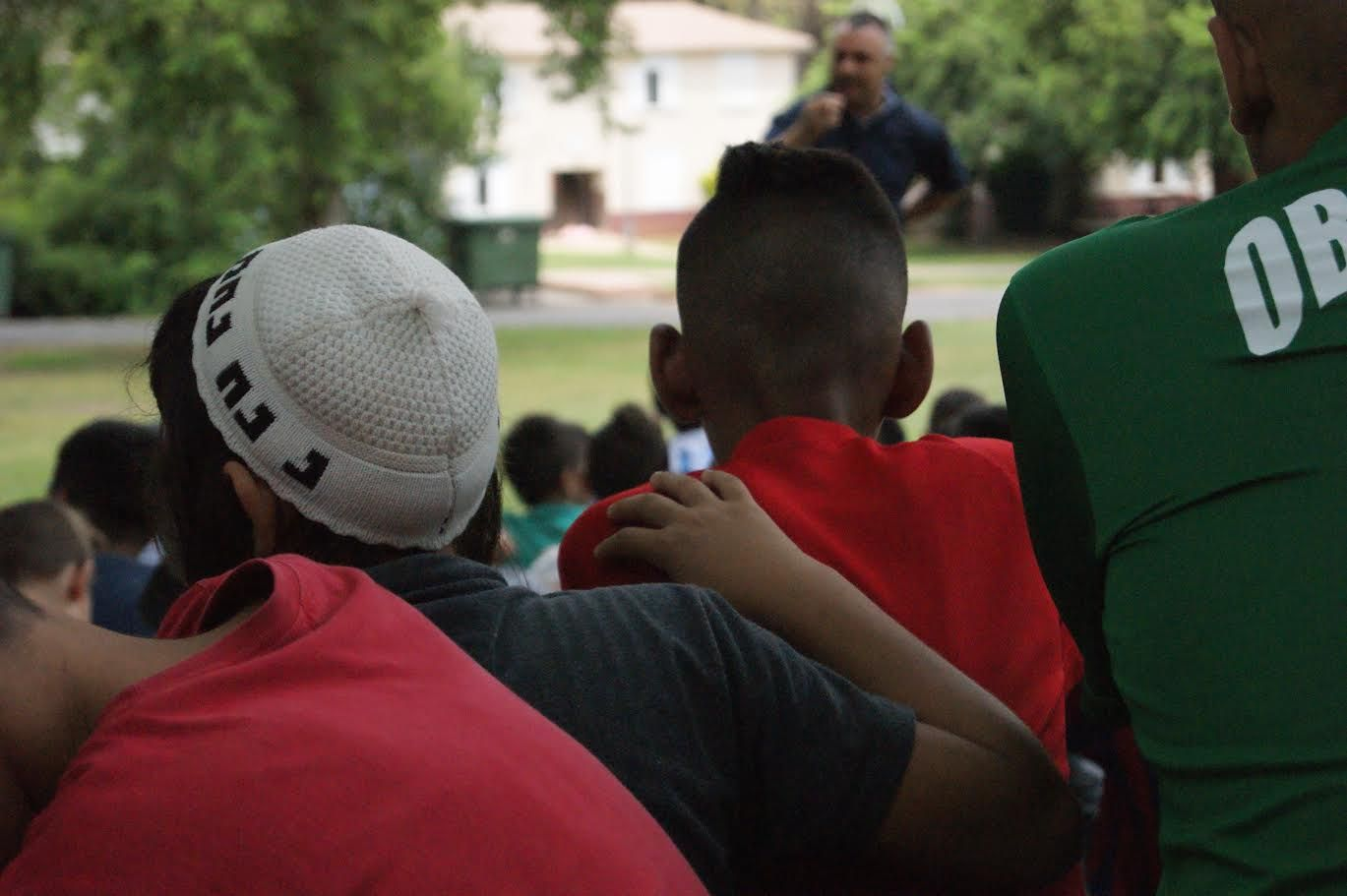Participants at the Soccer for Peace summer camp listen to a prep talk from head coach Fayad Shalabi