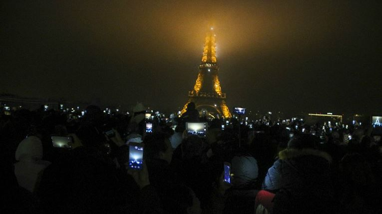 Revellers gather at the foot of the Eiffel Tower for the New Year's celebration on January 1, 2017 in Paris.