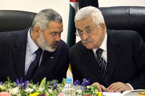 In this Sunday March 18, 2007 file photo, Palestinian Authority President Mahmoud Abbas, right, and Palestinian Prime Minister Ismail Haniyeh of Hamas, left, speak as they head the first cabinet meeting of the new coalition government at Abbas' office, in