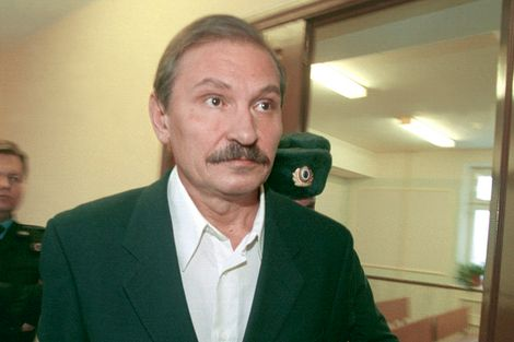 FILE - In this Tuesday, Dec. 19, 2000 file photo, ex-deputy director general of Aeroflot airlines company Nikolai Glushkov leaves the Lefortovsky court escorted by police officers, after the judge refused to release him on bail, in Moscow.
