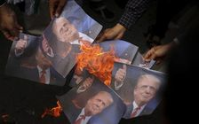 Muslim men burn portraits of US President Donald Trump and rally against his decision to recognize Jerusalem as Israel's capital in Banda Aceh, Indonesia, Friday, Dec. 8, 2017.