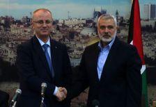 Hamas leader Ismail Haniyeh [R] shakes hands with Fatah leader Rami Hamdallah