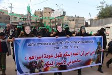 "Hamas militants march in Gaza with the faces of Israeli soldiers Oron Shaul, Hadar Goldin, and missing Ethiopian Avera Mengistu, holding banner reading: ""Mother and father, I will not return to you before Palestinian prisoners return home"""