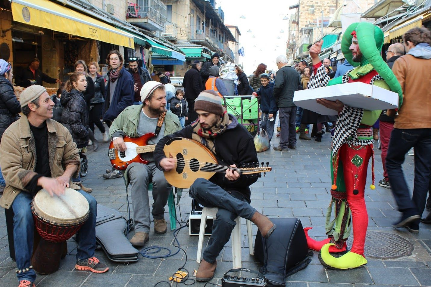 Itaï joue de l'oud, accompagné de djembé et de guitare bass, l'arlequin offre des beignets aux enfants, Mahane Yéhouda, Jérusalem, le 28 décembre 2016