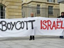 An anti-Israel activists holds up a banner calling for the boycott of Israel