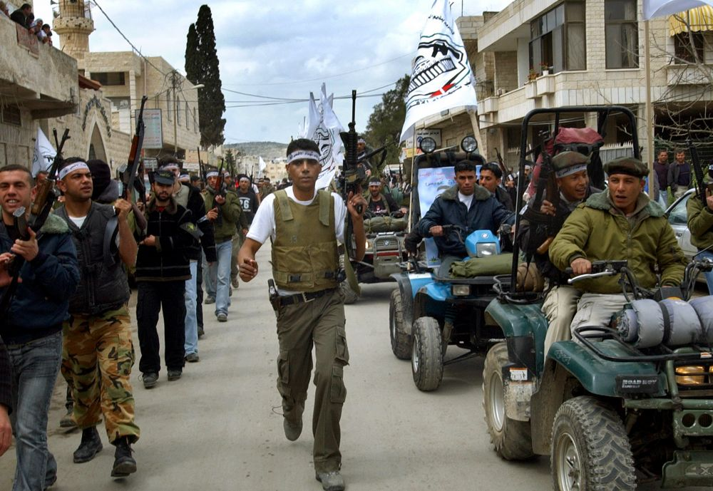 FILE--Zakaria Zubeidi, the local leader of the Al-Aqsa Martyrs Brigades and other militants march along the streets of the West Bank town of Jenin, Saturday April 2, 2005 during a rally to mark the 3rd anniversary of the assault by the Israeli army in Jen