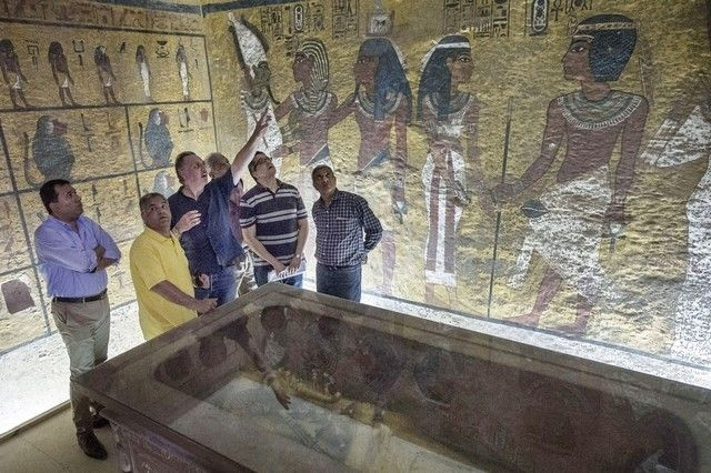 Egypt's minister of antiquities, Mamdouh Al Damati, second left, listens to British Egyptologist Nicholas Reeves, third left, near the sarcophagus of King Tutankhamun in his burial chamber in the Valley of the Kings, close to Luxor on September 28, 2015