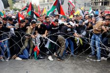 Protesters try to remove barbed wires that block a road leading to the U.S. embassy during a demonstration in Aukar, east of Beirut, Lebanon, Sunday, Dec. 10, 2017.