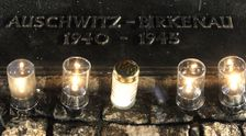 Candles burn by a memorial plaque at the Birkenau Nazi death camp in Oswiecim, Poland, Tuesday, Jan. 27, 2015, after the official remembrance ceremony.