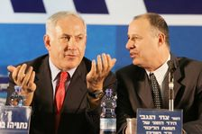 Candidate for the Likud party leadership Benjamin Netanyahu (L) speaks as to the temporary chairman of the party Tzahi Hanegbi looks on, during a party gathering in Tel Aviv, 24 November 2005.