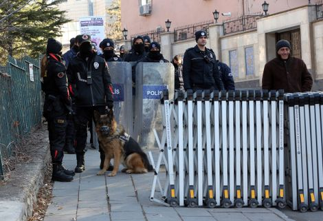 FILE- Riot police stand guard with their six-year-old German shepherd dog Venus as people gather to protest against Iran's support of the Syrian regime, outside the Iranian embassy in Ankara, Turkey, Thursday, Dec. 15, 2016.