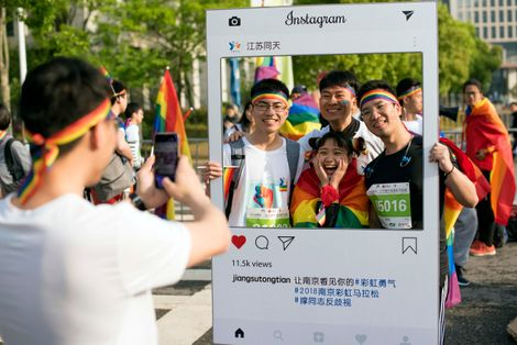"In this April 15, 2018 photo released by Jiangsu Tongtian Volunteer Group, participants pose for photos during a ""Rainbow Marathon,"" organized months earlier, to raise awareness of LGBT issues in Nanjing in eastern China's Jiangsu province."