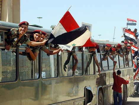 Syrian soldiers lean out of the windows of their bus at Jdaidet Yabous a crossing point on the Syrian-Lebanese border, 45 kilometers (28 miles) west of Damascus, the Syrian capital, Tuesday, April 26, 2005 as they celebrate their return from Lebanon. Syri