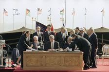 U.S. President Bill Clinton, center, Israeli Prime Minister Yitzhak Rabin, left, and Jordanian Prime Minister Abdul-Salam Majali, right, sign the peace treaty between Israel and Jordan during a ceremony at the Wadi Araba Israel/Jordan border crossing near