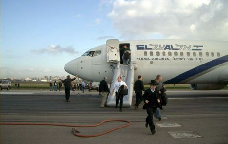 Passengers and crew members flee away of an El Al aircraft at Ben Gurion International Airport near Tel Aviv Sunday, March 25, 2007. An El Al jet taxiing before takeoff at Ben Gurion International Airport filled with smoke on Sunday, forcing passengers an