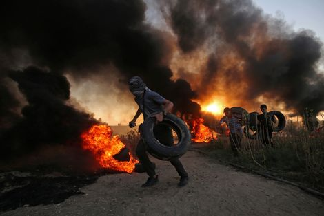 Black smoke from burning tires hangs in the sky as Palestinian protesters hurl stones toward Israeli troops during a protest at the Gaza Strip's border with Israel, Friday, Oct. 12, 2018
