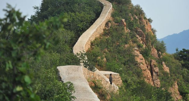 This picture taken on September 21, 2016 shows a villager walking on a paved-over section of the Great Wall of China at Suizhong, in China's northeast Liaoning province
