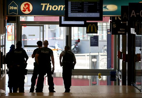 Police forces stand at the Cologne, western Germany, main station Monday, Oct. 15, 2018, after they have closed parts of the station because of a hostage situation. Police said that incident appears to have started Monday at a pharmacy inside the train st