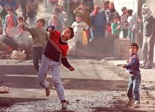 Palestinians throw stones in Ramallah as part of the First Intifada in 1989
