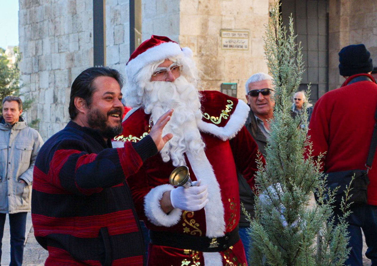 Santa poses for a photo while helping to give out free Christmas trees in Jerusalem on December 20, 2016