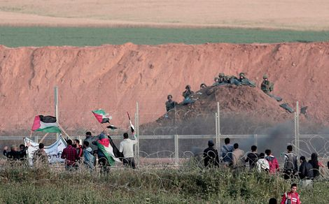 FILE - In this Wednesday, April 4, 2018 file photo, Palestinian protesters wave flags in front of Israeli soldiers on Gaza's border with Israel near Beit Lahiya