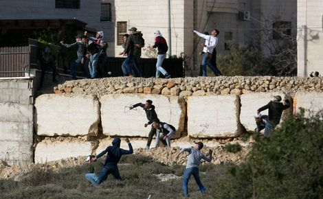 Palestinians throw rocks as Israeli soldiers conduct a search for suspects of a shooting attack yesterday in the West Bank City of Ramallah, Monday, Dec. 10, 2018. Israeli officials say seven people have been wounded, one critically, in a shooting by a su
