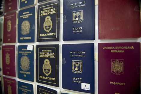 "Fake passports are displayed at the immigration bureau in Bangkok on February 10, 2016 after Thai police broke up a major fake passport ring led by an Iranian known as ""The Doctor"" which sent thousands of passports to Middle Eastern customers trying to en"