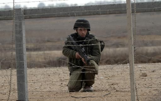 An Israeli soldier keeps watch next to the security fence standing on the Gaza border with Israel, east of Khan Yunis, in the southern Gaza Strip, on November 23, 2012