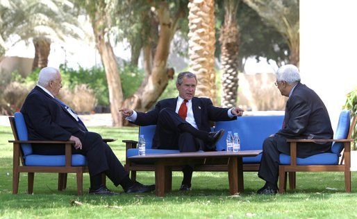 President George W. Bush, center, discusses the Middle East peace process with Prime Minister Ariel Sharon of Israel, left, and Palestinian President Mahmoud Abbas in Aqaba, Jordan, 4 June 2003.