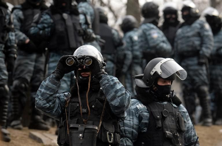 A Ukrainian police officer looks through binoculars at opposition activists after violent clashes in Kiev, on January 21, 2014