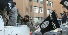 Islamic state group militants drive through the Syrian city of Raqa