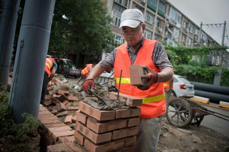 عامل بناء خارج مجمع في بكين في 16 آب/اغسطس 2017