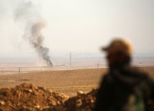 Smoke billows in the background as a member of the Syrian Democratic Forces (SDF) looks on in the village of Abu al-Ilaj, some 50 kilometres (30 miles) north of Raqa, on November 7, 2016