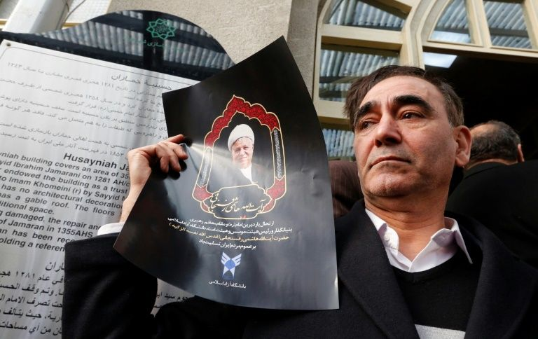 A mourner holds a poster of former Iranian president Akbar Hashemi Rafsanjani during a ceremony at the Jamaran mosque in Tehran, on January 9, 2017