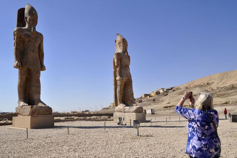 A tourist takes a picture of two colossal statues of Pharaoh Amenhotep III in Luxor on December 14, 2014