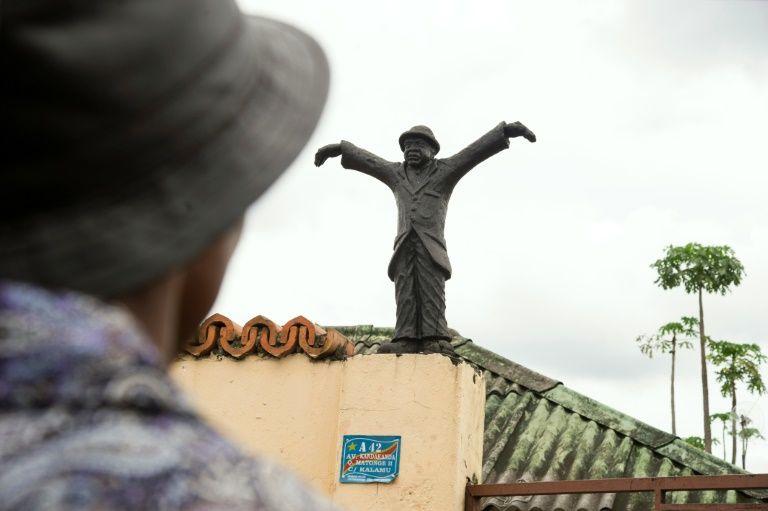 """Un homme se tient le 25 avril 2016 à Kinshasa devant la maison d'enfance du """"roi de la rumba congolaise"""", Papa Wemba, décédé la veille"""